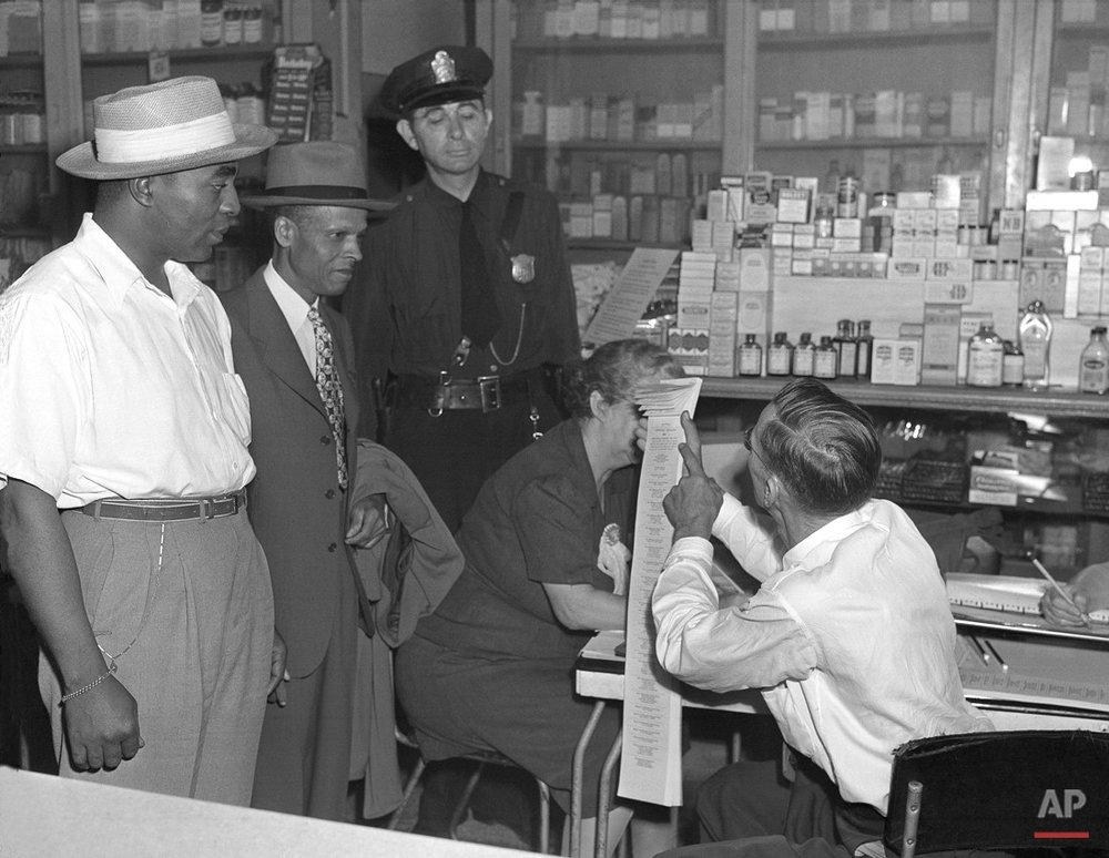 W. R. Owens, right, election official tells two African Americans who tried in vain to vote in Atlanta's city Democratic white primary on Sept. 5, 1945, that the primary is for white persons only and points to the top of the ballot which so states. They are Lewis K. McGuire, left, World War II veteran, and S. M. Lewis, a physician. Beside them stands policeman Roy Wall. (AP Photo/McD)