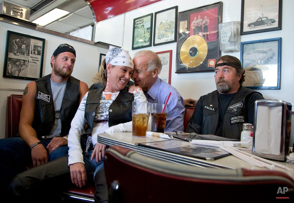 In this Sept. 9, 2012 photo, Vice President Joe Biden talks to customers, including a woman who pulled up her chair in front of the bench Biden was sitting on, during a stop at Cruisers Diner in Seaman, Ohio. Let's be clear: the biker chick in the bandana and leather vest is NOT sitting in Biden's lap. But it sure looks like it. The vice president plunked himself down with some bikers in a diner in Seaman, Ohio, this fall, and leaned in close behind one woman, grabbing on to her shoulders as they posed for photos. That's Joe. (AP Photo/Carolyn Kaster)