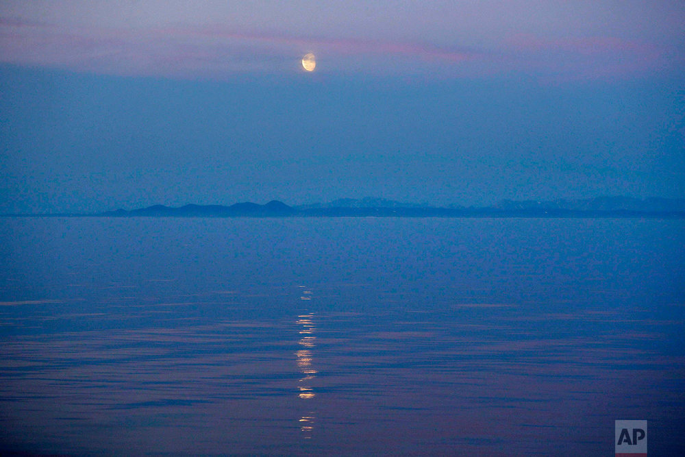 The moon rises over the coast of Alaska as the Finnish icebreaker MSV Nordica sails along the international date line through the Bering Strait, Friday, July 14, 2017. The international date line is an imaginary border that runs through the middle of the Pacific Ocean and marks the boundary between calendar dates. Crossing the line from east to west, people would need to set their clocks forward by a day. Crossing from west to east, they would need to set it back by a day. (AP Photo/David Goldman)