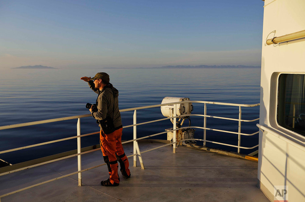 Researcher Ari Laakso shields his eyes from the midnight sun while approaching the American island of Little Diomede, Alaska, and the Russian island of Big Diomede, as the Finnish icebreaker MSV Nordica sails along the international date line through the Bering Strait, Friday, July 14, 2017. The international date line divides the two islands, putting them currently 20 hours apart despite roughly 2.4 miles (3.8 kilometers) between them. (AP Photo/David Goldman)