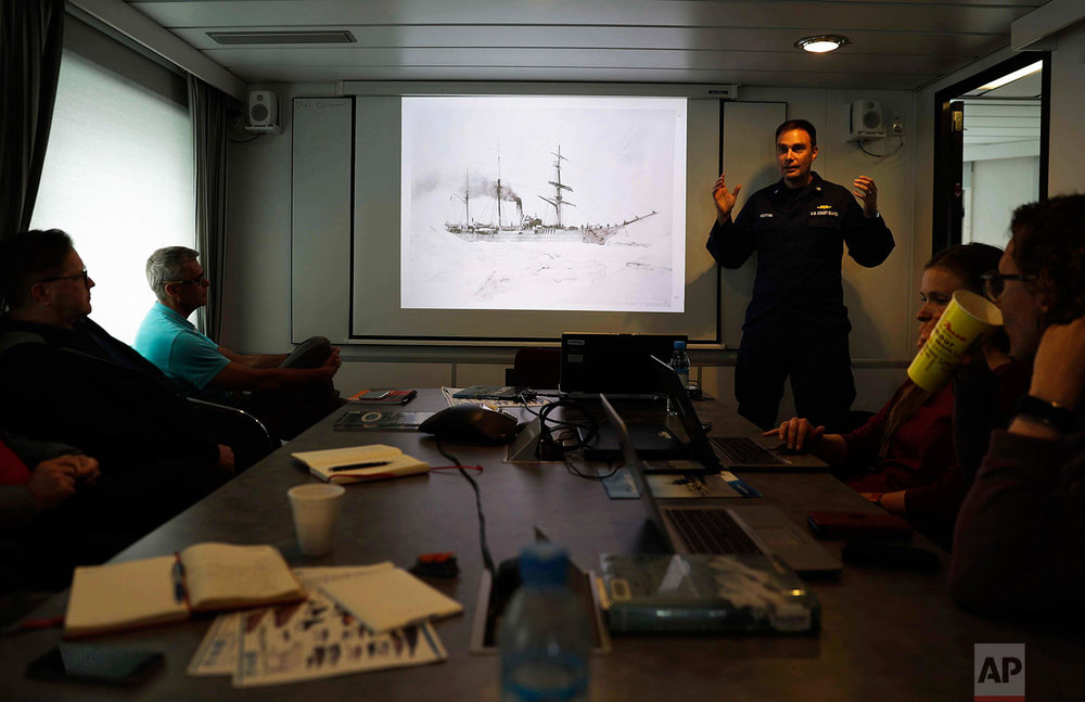 Cmdr. Bill Woityra, manager for domestic and polar icebreaking for the U.S. Coast Guard, right, gives a presentation on the history of U.S. ice breaking aboard the Finnish icebreaker MSV Nordica as it sails in the North Pacific Ocean toward the Bering Sea, Sunday, July 9, 2017. (AP Photo/David Goldman)