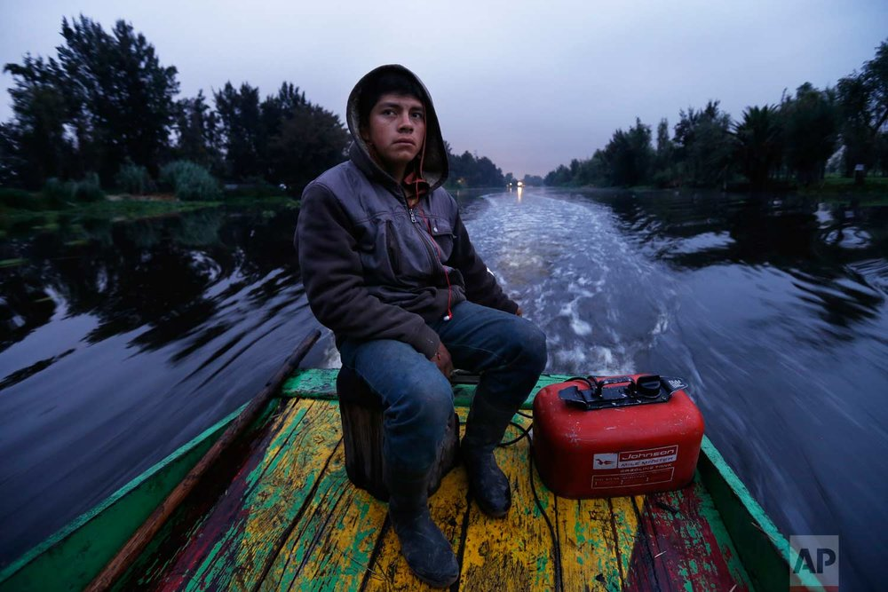 "In this July 13, 2017 photo, Gerardo Cristobal navigates his boat as he ferries farmers and laborers to their floating farms called ""chinampas"" in Xochimilco, Mexico City.  (AP Photo/Marco Ugarte)"