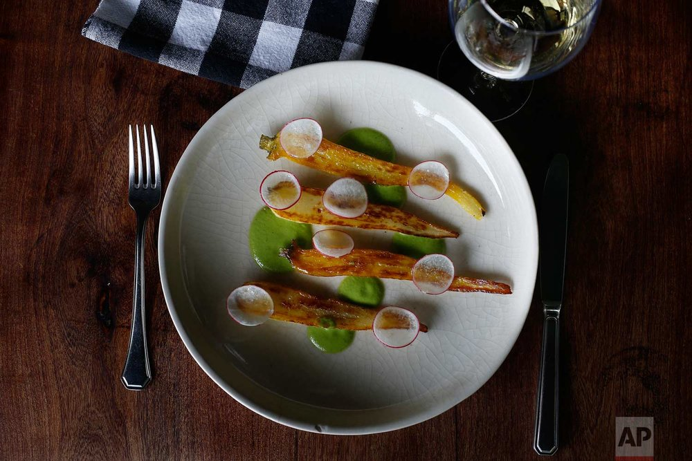 This July 14, 2017 photo shows a plate garnished with chinampa-grown roasted yellow carrots with asparagus puree, prepared by chef Eduardo Garcia, founder of Maximo Bistrot and a former U.S. migrant worker, at his restaurant in Mexico City. (AP Photo/Marco Ugarte)