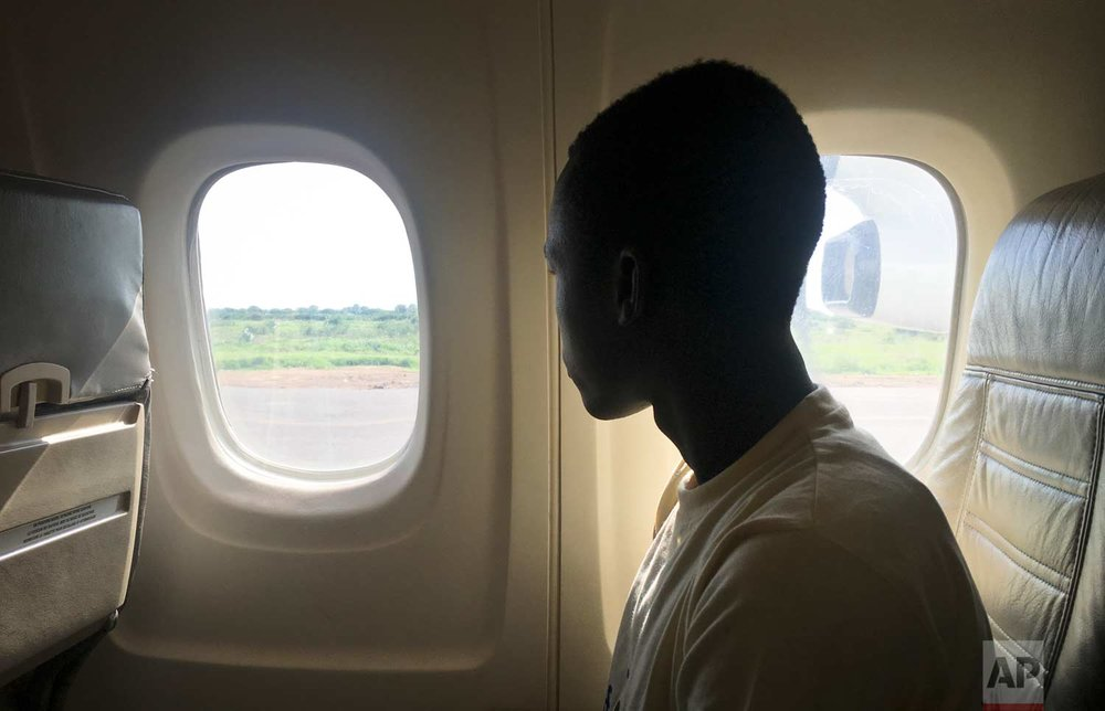 In this photo taken Friday, May 26, 2017, former child soldier James looks through an airplane window as he arrives to be reunited with his mother who had thought he was dead, in Bentiu, South Sudan. (AP Photo/Sam Mednick)