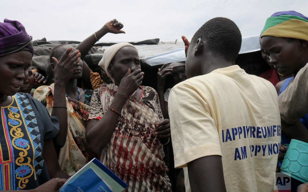 In this photo taken Friday, May 26, 2017, former child soldier James, center-right, is surrounded by family and friends as he is welcomed home by his community and meets his mother for the first time in 3 years, at a protection of civilians site in Bentiu, South Sudan. (AP Photo/Sam Mednick)