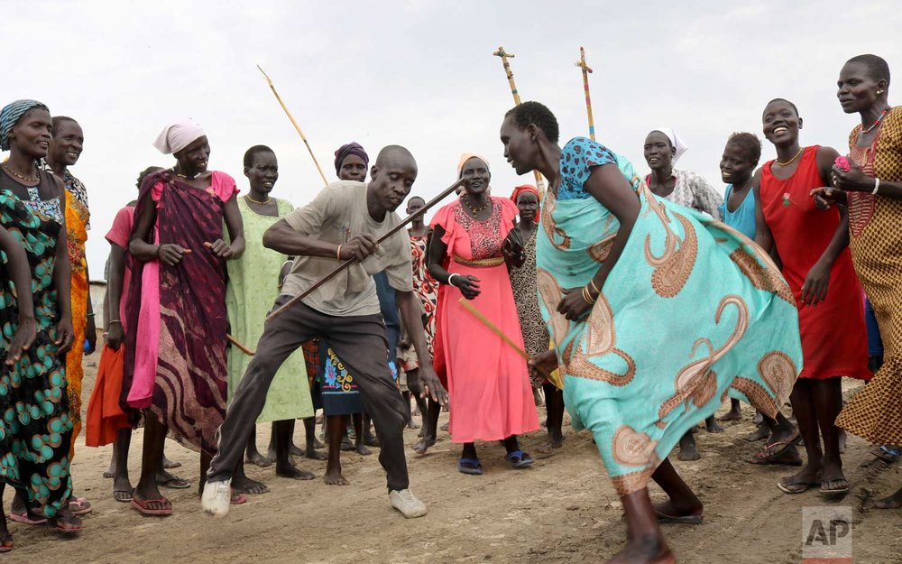 In this photo taken Friday, May 26, 2017, family and friends dance through the streets singing and chanting to honor the return of former child soldier James, after he is reunited with his mother and sees her for the first time in 3 years, at a protection of civilians site in Bentiu, South Sudan. (AP Photo/Sam Mednick)