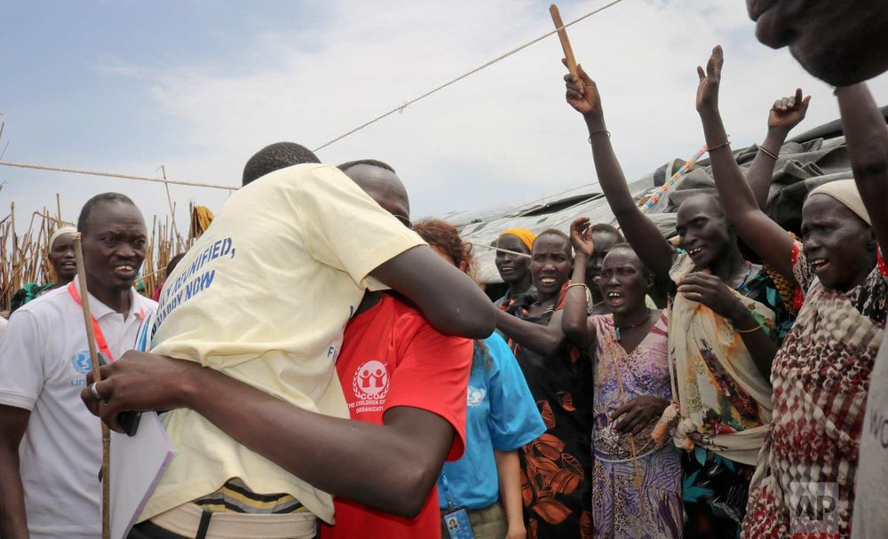 In this photo taken Friday, May 26, 2017, former child soldier James, center-left, is hugged by a community member as he is welcomed home and sees his mother for the first time in 3 years, at a protection of civilians site in Bentiu, South Sudan. (AP Photo/Sam Mednick)