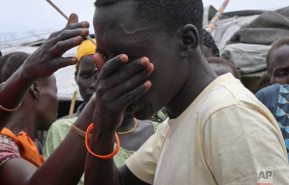 In this photo taken Friday, May 26, 2017, former child soldier James cries uncontrollably as he is reunited with his mother for the first time in 3 years, while family and friends brush their hands over his face in a Nuer tradition that wishes him a long life, at a protection of civilians site in Bentiu, South Sudan. (AP Photo/Sam Mednick)