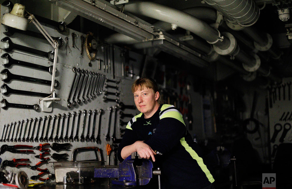 "Electrician Kaija Peuhkuri, 42, stands for a portrait in the machine shop of the Finnish icebreaker MSV Nordica as the ship sails north in the Bering Sea toward the Arctic, Wednesday, July 12, 2017. Peuhkuri started as a cook on ships over 20 years ago before going back to school and becoming an electrician on icebreakers in 2009. Growing up on a farm working on machines, she prefers working away at sea as opposed to commuting to a job at home. ""I don't want to do this every morning,"" she said of having to drive to work. ""Here, I come downstairs every morning, have a cup of coffee and I'm at work."" (AP Photo/David Goldman)"