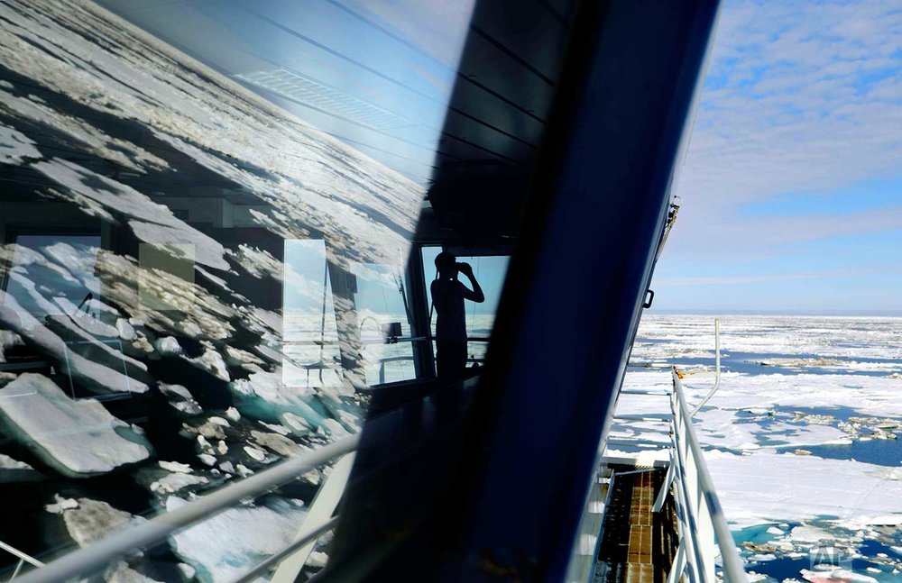 Trainee David Kullualik, of Iqaluit, Nunavut, Canada, looks through binoculars from the bridge of the Finnish icebreaker MSV Nordica as it sails through ice floating on the Chukchi Sea off the coast of Alaska while traversing the Arctic's Northwest Passage, Sunday, July 16, 2017. (AP Photo/David Goldman)