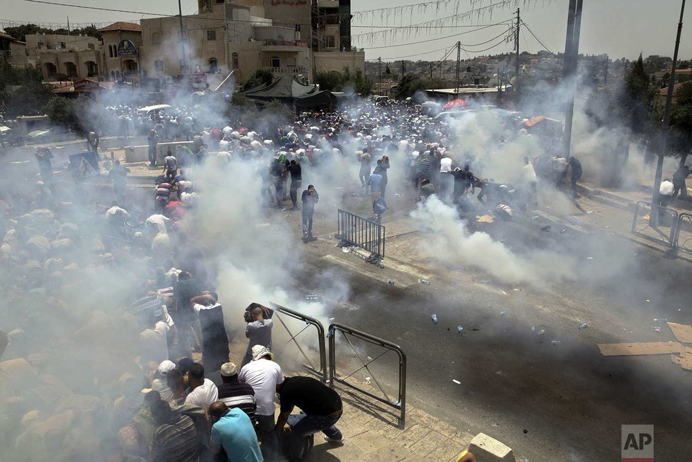 Palestinians run away from tear gas fired by Israeli forces in Jerusalem, on Friday, July 21, 2017. (AP Photo/Mahmoud Illean)