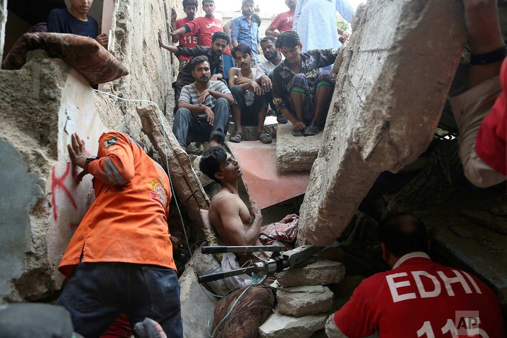 Rescue workers and volunteers try to free a trapped man in Karachi, Pakistan, Tuesday, July 18, 2017. (AP Photo/Shakil Adil)