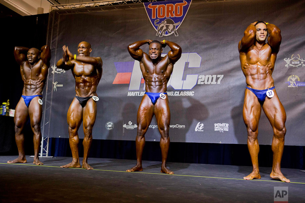 In this July 23, 2017 photo, Haitian bodybuilder Spely Laventure, center, performs alongside Dominican Jose Solano, right, and other Haitian athletes during a bodybuilding competition between Haiti and Dominican Republic in Port-au-Prince, Haiti. (AP Photo/Dieu Nalio Chery)