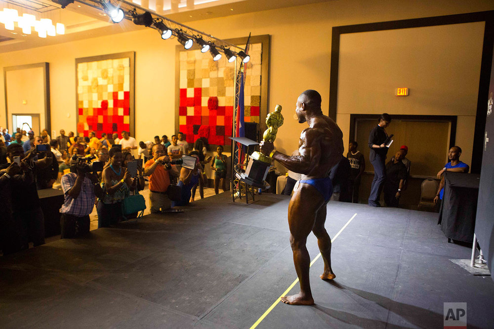 In this July 23, 2017 photo, Haitian bodybuilder Spely Laventure holds his trophy up as photographers take his picture after winning the first bodybuilding competition between Haiti and Dominican Republic in Port-au-Prince, Haiti. (AP Photo/Dieu Nalio Chery)