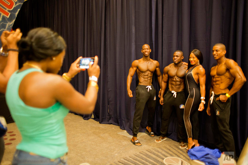 In this July 23, 2017 photo, Haitian bodybuilder Spely Laventure, third from right, takes pictures with a fan and fellow Haitian bodybuilders before a competition between Haiti and Dominican Republic in Port-au-Prince, Haiti. (AP Photo/Dieu Nalio Chery)