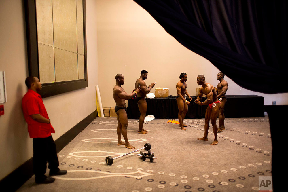 In this July 23, 2017 photo, Haitian bodybuilders take pictures before the start of a bodybuilding competition between Haiti and Dominican Republic in Port-au-Prince, Haiti. (AP Photo/Dieu Nalio Chery)
