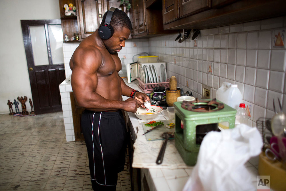 In this July 21, 2017 photo, Haitian bodybuilder Spely Laventure prepares a special breakfast at his home in Port-au-Prince, Haiti. (AP Photo/Dieu Nalio Chery)