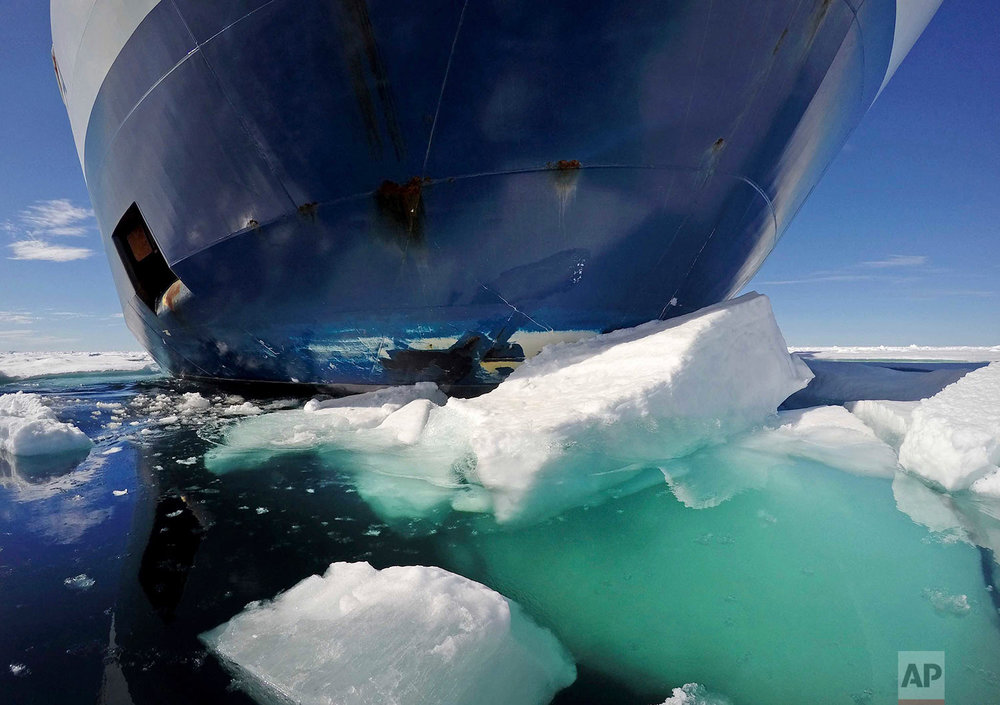 The bow of the Finnish icebreaker MSV Nordica pushes down sea ice as it sails through the Victoria Strait while traversing the Arctic's Northwest Passage, Friday, July 21, 2017. The MSV Nordica is equipped with several heavy-duty engines and a hardened bow and hull that allow it either to drive through thin layers of ice or to crush thicker sheets by rising onto the ice with the help of its rounded hull. The ship's massive weight breaks the ice from above. (AP Photo/David Goldman)