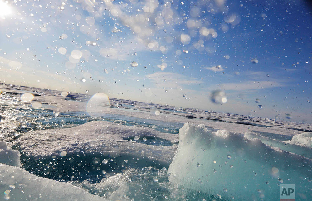 Water sprays as a block of sea ice is broken from the hull of the Finnish icebreaker MSV Nordica as it sails the Victoria Strait while traversing the Arctic's Northwest Passage, Friday, July 21, 2017. (AP Photo/David Goldman)