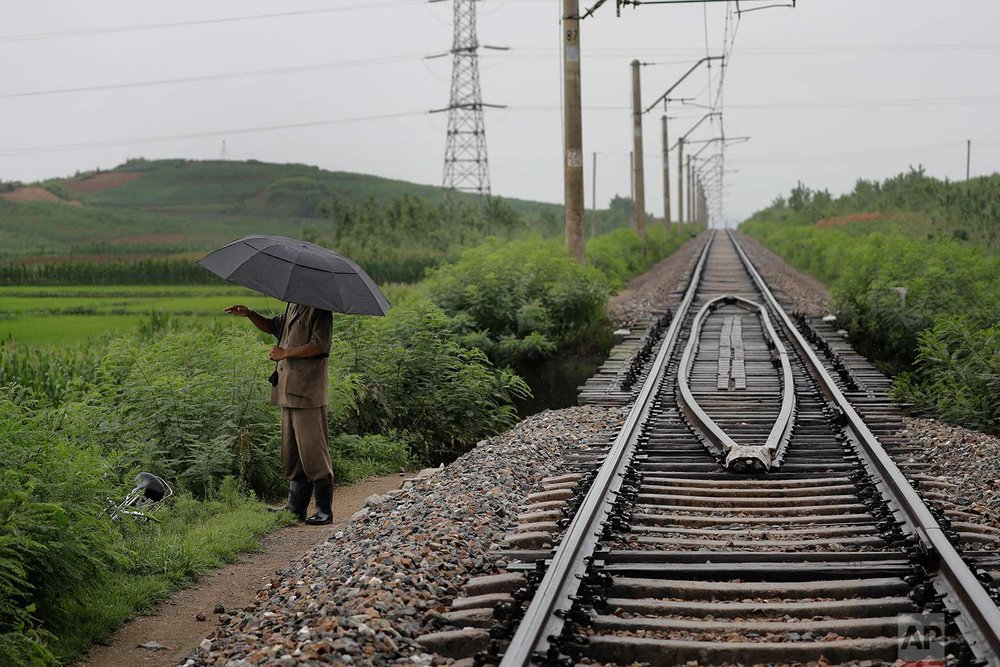 In this Friday, July 21, 2017, photo, a man stands near the pathway leading to where an unexploded bomb was found near the railway which runs through Hamhung from Pyongyang to the northeastern port of Chongjin. (AP Photo/Wong Maye-E)