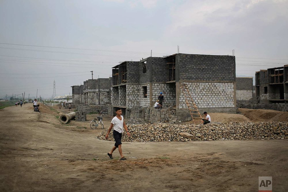 In this Friday, July 21, 2017, photo, a man walks past a construction site on the outskirts of Hamhung, North Korea's second-largest city, where construction workers unearthed a rusted but still potentially deadly mortar round in February. North Korea is just one of many countries still dealing with the explosive legacy of major wars. But the three-year Korean War, which ended in what was supposed to be a temporary armistice on July 27, 1953, was one of the most brutal ever fought. (AP Photo/Wong Maye-E)