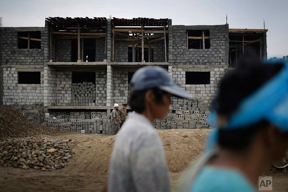 In this Friday, July 21, 2017, photo, women walk past a construction site on the outskirts of Hamhung, North Korea's second-largest city, where construction workers unearthed a rusted but still potentially deadly mortar round in February. (AP Photo/Wong Maye-E)