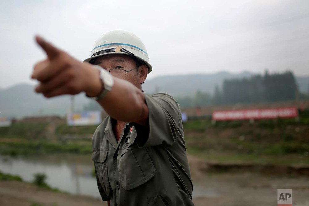 In this Friday, July 21, 2017, photo, Choe Chang Sok, 52, senior staff in charge of construction, gestures towards a construction site on the outskirts of Hamhung, North Korea's second-largest city, where he and fellow workers unearthed a rusted but still potentially deadly mortar round in February. (AP Photo/Wong Maye-E)
