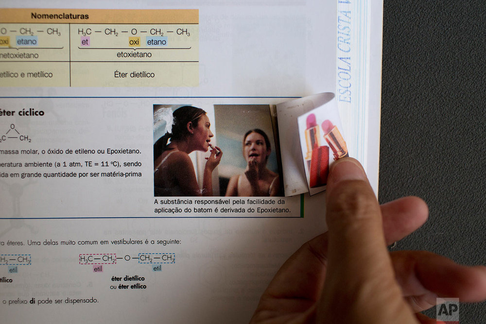This Thursday, March 30, 2017 photo shows a page in a schoolbook with a printed picture of a woman applying lipstick covered with another image in Belo Horizonte, Brazil. This and other schoolbooks used by members of the Word of Faith Fellowship church in Brazil show heavy redactions. Instead of human sexuality, for example, the life cycle is taught via plant reproduction. (AP Photo/Silvia Izquierdo)
