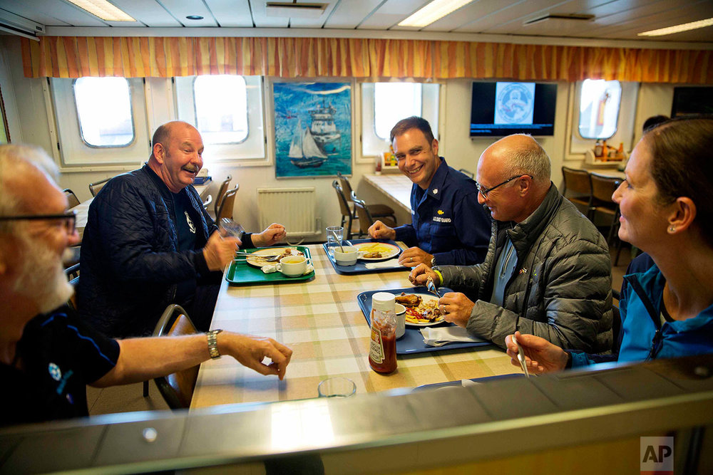 """In this Monday, July 10, 2017 photo, ice navigator Capt. David """"Duke"""" Snider, from left, Canadian Coast Guard Capt. Victor Gronmyr, U.S. Coast Guard Cmdr. Bill Woityra, assistant ice navigator Nigel Greenwood, and biologist Paula von Weller talk over dinner in the mess hall aboard the Finnish icebreaker MSV Nordica as it sails the North Pacific Ocean to traverse the Northwest Passage through the Canadian Arctic Archipelago. (AP Photo/David Goldman)"""