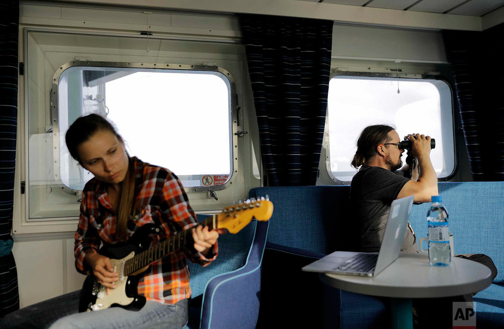 "In this Friday, July 7, 2017 photo, researcher Daria Gritsenko, left, plays ""Hotel California"" on the guitar as fellow researcher Ari Laakso, right, looks from aboard the Finnish icebreaker MSV Nordica as it sails the North Pacific Ocean to traverse the Northwest Passage through the Canadian Arctic Archipelago. (AP Photo/David Goldman)"