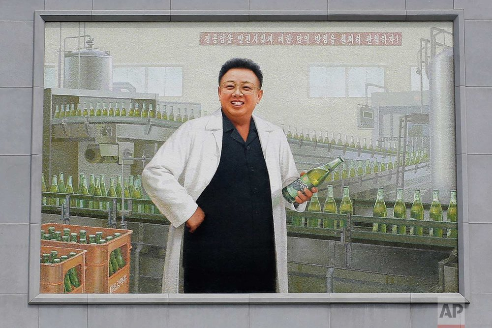 In this Wednesday, July 26, 2017, photo, a mural of the late North Korean leader Kim Jong Il in a white lab coat holding up a bottle of beer is seen at the entrance of the Taedonggang Brewery in Pyongyang, North Korea. (AP Photo/Wong Maye-E)
