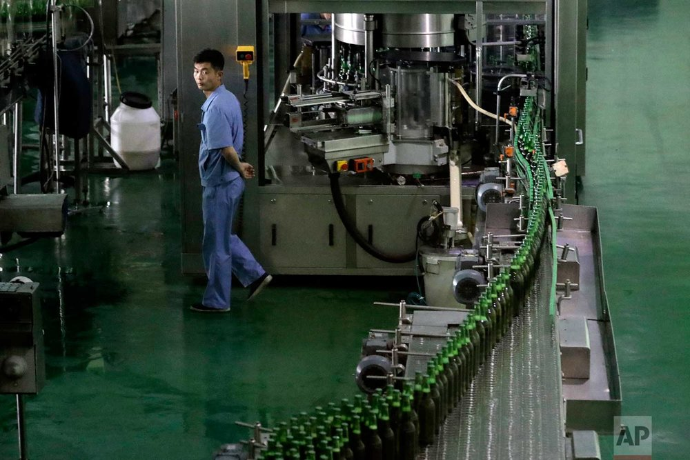 In this Wednesday, July 26, 2017, photo, a worker monitors a conveyor belt where bottles of beer are transported at the Taedonggang Brewery in Pyongyang, North Korea. (AP Photo/Wong Maye-E)