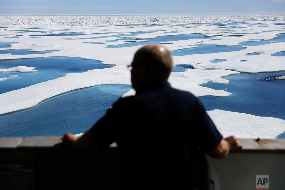 Second officer Juha Tuomi looks out from Finnish icebreaker MSV Nordica as it sails into floating sea ice on the Victoria Strait while traversing the Northwest Passage in the Canadian Arctic Archipelago, Friday, July 21, 2017. Sea ice plays an important role in the global climate system by cooling the surrounding water and air. (AP Photo/David Goldman)