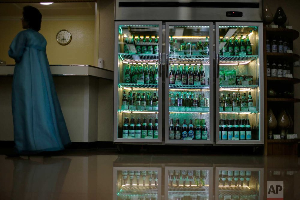 In this Wednesday, July 26, 2017, photo, a factory guide stands next to a refrigerator containing different types of beer produced at the Taedonggang Brewery in Pyongyang, North Korea. (AP Photo/Wong Maye-E)
