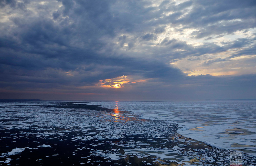 The sun sets over melting sea ice on Peel Sound along the Northwest Passage in the Canadian Arctic Archipelago, Sunday, July 23, 2017. Because of global warming, more sea ice is being lost each summer than is being replenished in winters. Although sea ice is likely to continue forming each winter it may be restricted to even higher latitudes. Less sea ice coverage also means that less sunlight will be reflected off the surface of the ocean in a process known as the albedo effect. The oceans will absorb more heat, further fueling global warming. (AP Photo/David Goldman)