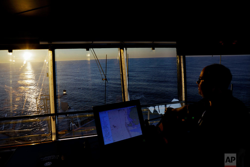 The sun lingers above the Bering Sea at midnight as second officer Juha Tuomi overseas the navigation of the Finnish icebreaker MSV Nordica as it sails toward the Canadian Arctic Archipelago to traverse the Northwest Passage, early Thursday, July 13, 2017. Tuomi, who has worked on boats for over 37 years and saw his first midnight sun in Greenland in 1983, is making his first traverse through the Northwest Passage. (AP Photo/David Goldman)