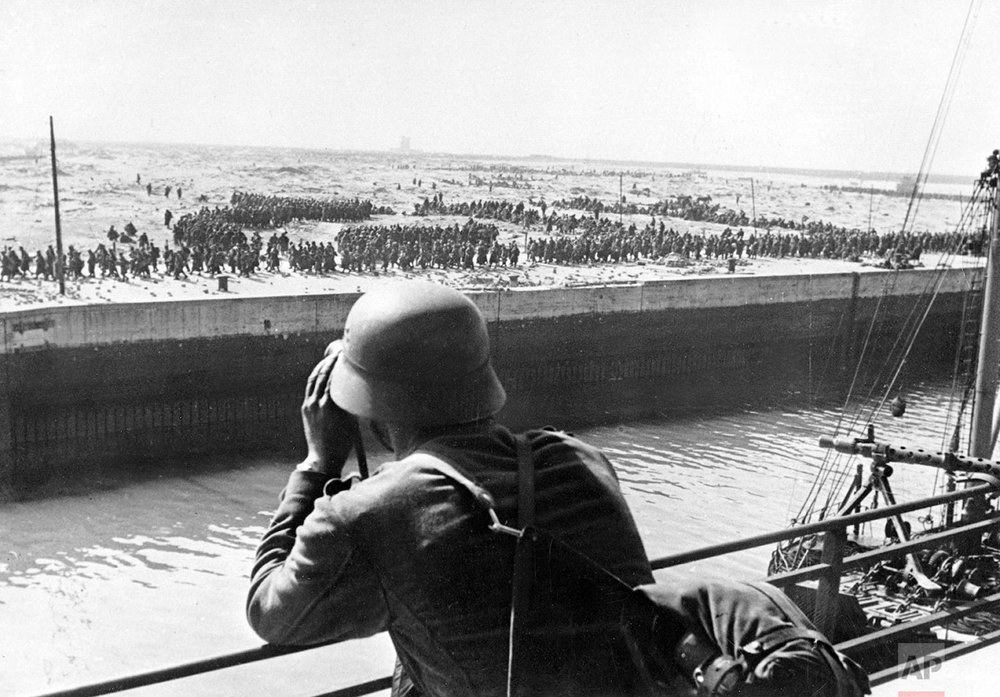 A member of the German Wehrmacht looks through a pair of binoculars on French and British prisoners of war in the harbor of Dunkirk on the Western Front in France, June 1940. (AP Photo/DPA)