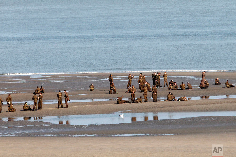"Actors wait on the beach before filming a scene for the film, ""Dunkirk,"" in Dunkirk, northern France, Thursday, May 26, 2016. The film, directed by Christopher Nolan, tells the story of the Dunkirk evacuation, which took place at the beginning of World War II. (AP Photo/Michel Spingler)"