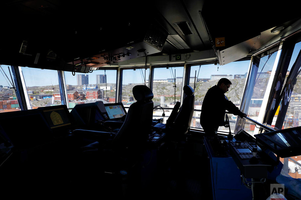 Master Mariner Jyri Viljanen, captain of the Finnish icebreaker MSV Nordica, looks out from the bridge after docking the ship in Nuuk, Greenland, as it arrives after traversing the Northwest Passage through the Canadian Arctic Archipelago, Saturday, July 29, 2017. After 24 days at sea and a journey spanning more than 10,000 kilometers (6,214 miles), the MSV Nordica has set a new record for the earliest transit of the fabled Northwest Passage. The once-forbidding route through the Arctic, linking the Pacific and the Atlantic oceans, has been opening up sooner and for a longer period each summer due to climate change. (AP Photo/David Goldman)
