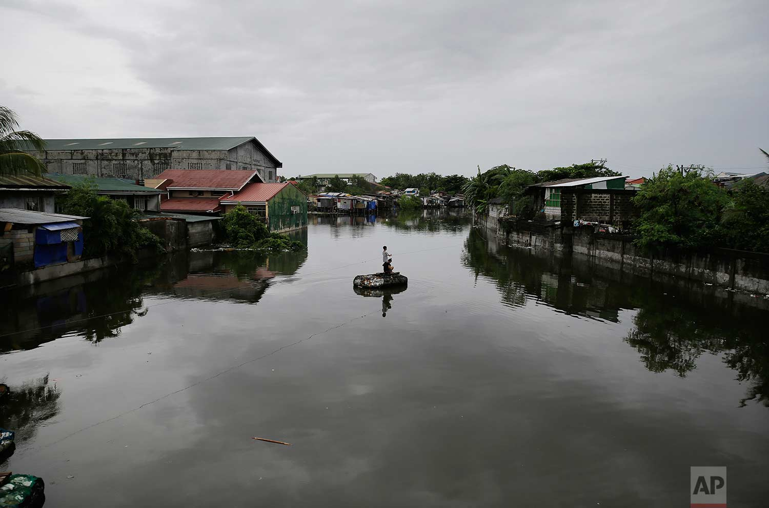 Residents pull a rope in an improvised raft to cross a swollen river caused by tropical storm Gorio on the outskirts of Manila, Philippines on Wednesday, July 26, 2017. (AP Photo/Aaron Favila)