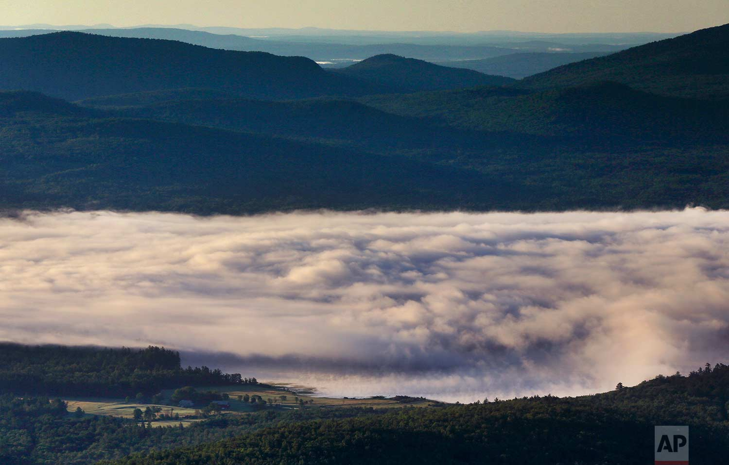 A billowy layer of fog hovers over Webb Lake on a chilly morning where the temperature dropped into the mid-40s, Wednesday, July 26, 2017, in Weld, Maine. (AP Photo/Robert F. Bukaty)