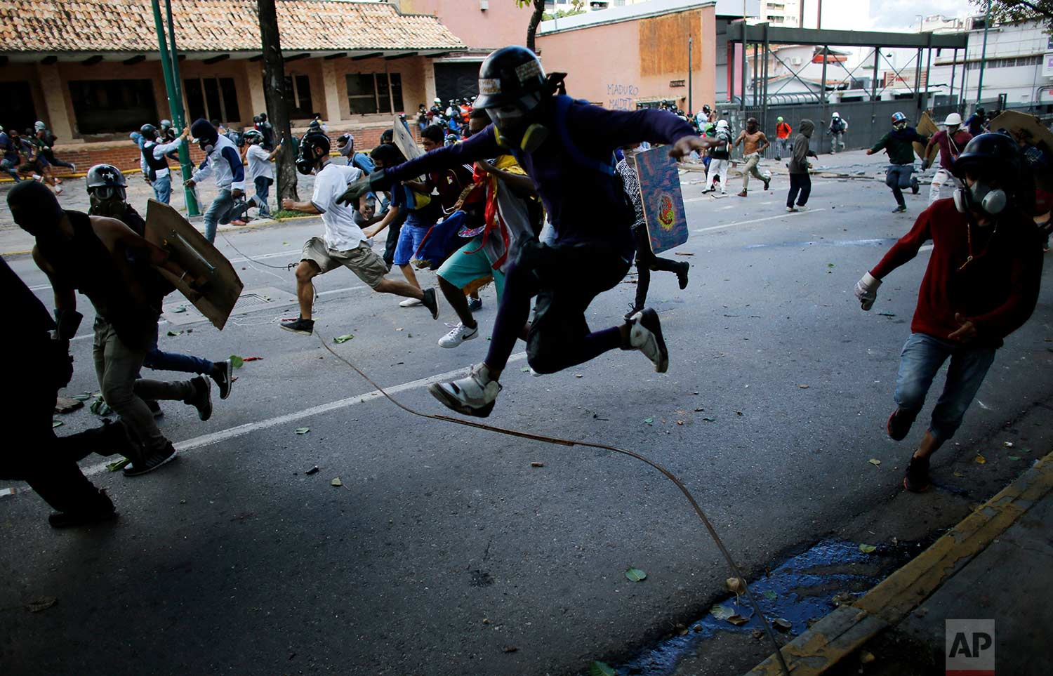 Anti-government protesters run from advancing Venezuelan Bolivarian National Guard officers on the first day of a 48-hour general strike in protest of government plans to rewrite the constitution, in Caracas, Venezuela, Wednesday, July 26, 2017. (AP Photo/Ariana Cubillos)