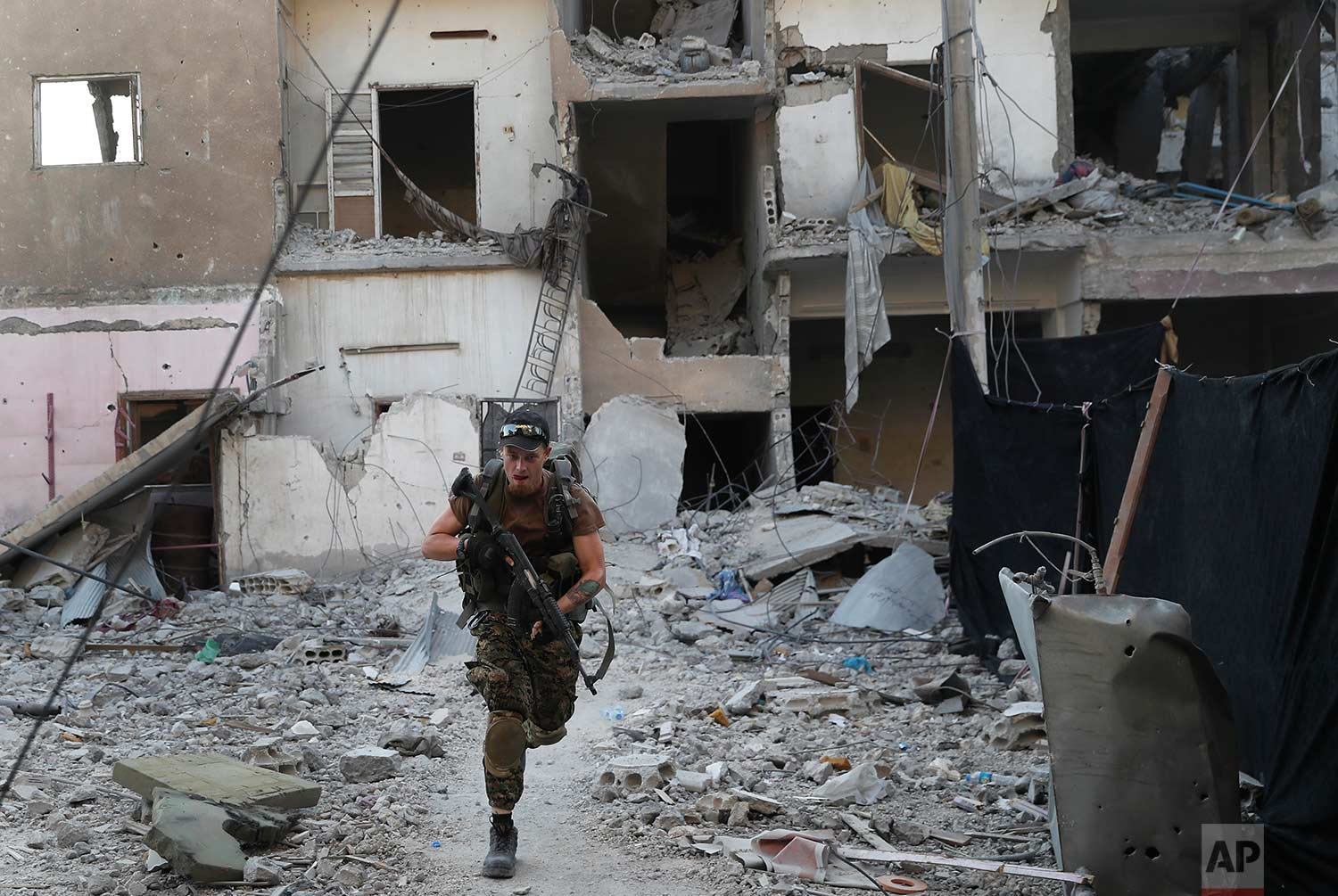 A U.S.-backed Syrian Democratic Forces fighter runs in front of a damaged building as he crosses a street on the front line, in Raqqa city, Syria, Thursday, July 27, 2017. (AP Photo/Hussein Malla)