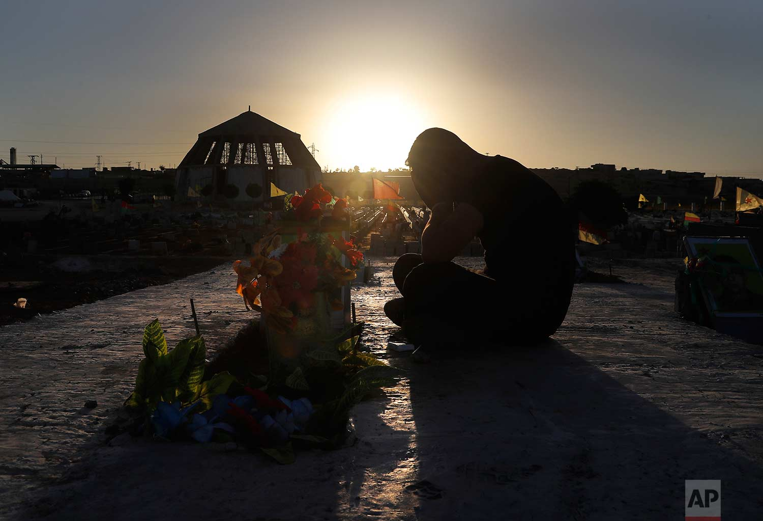 A Kurdish man mourns as he sits next to the grave of his friend who was killed while fighting against Islamic State militants in Raqqa, at a cemetery in Kobani, Syria, Friday, July 28, 2017. (AP Photo/Hussein Malla)