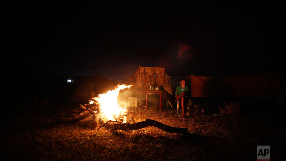 In this July 20, 2017 photo, a cowboy gets warm next to the camp fire, the night before the ascent to the Serra da Boa Vista, during the Ox Cart Festival in Vazante, Minas Gerais state, Brazil. The trip is a moving festival, a reminder of a rural world that existed during the colonial period, when the Portuguese began to occupy new lands in the interior of the country. (AP Photo/Eraldo Peres)