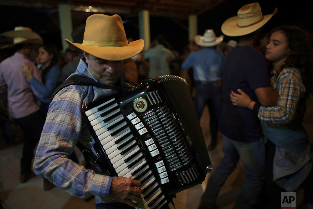 "In this July 20, 2017 photo, ""Dionisio of the Accordion,"" plays during the dance at the camp, the night before the ascent to the Serra da Boa Vista, during the Ox Cart Festival in Vazante, Minas Gerais state, Brazil. Dionisio plays regional favorites to the delight of the partygoers. (AP Photo/Eraldo Peres)"