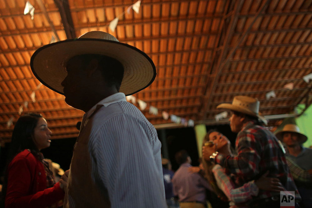 In this July 20, 2017 photo, cowboys dance during the ball at the camp, the night before the ascent to the Serra da Boa Vista, during the Ox Cart Festival in Vazante, Minas Gerais state, Brazil. The festival lasts three days and is a reminder of a rural world that existed during the colonial period, when the Portuguese began to occupy new lands in the interior of the country. (AP Photo/Eraldo Peres)