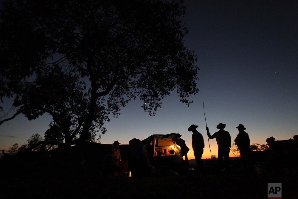 In this July 21, 2017 photo, cowboys have a chat at sunrise, before the ascent of the Serra da Boa Vista, during the Ox Cart Festival in Vazante, Minas Gerais state, Brazil. The ox drivers have a a hearty breakfast consisting of beef, coffee with milk and biscuits before starting on their way. (AP Photo/Eraldo Peres)