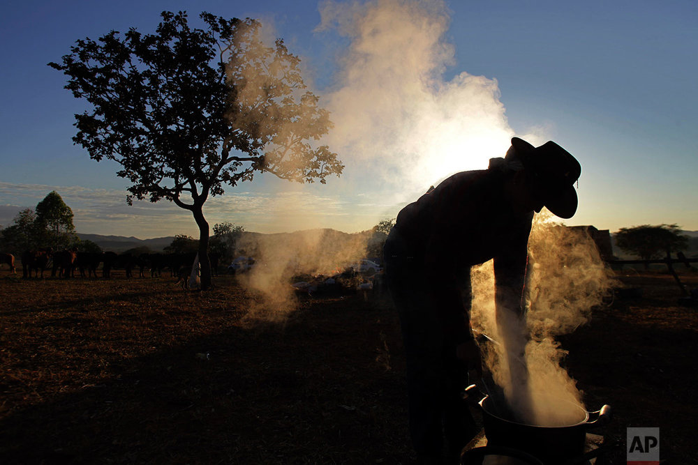 In this July 21, 2017 photo, a woman prepares breakfast on the camp fire at sunrise, before the ascent to the Serra da Boa Vista, during Ox Cart Festival inVazante, Minas Gerais state, Brazil. Farmers in the region use the corn harvest period in July to revive the tradition of traveling hundreds of miles in their ox carts. (AP Photo/Eraldo Peres)