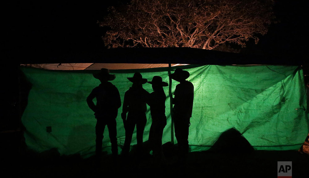 In this July 20, 2017 photo, youths talk during the night before the trip to the Serra da Boa Vista, during the Ox Cart Festival in Vazante, Minas Gerais state, Brazil. (AP Photo/Eraldo Peres)